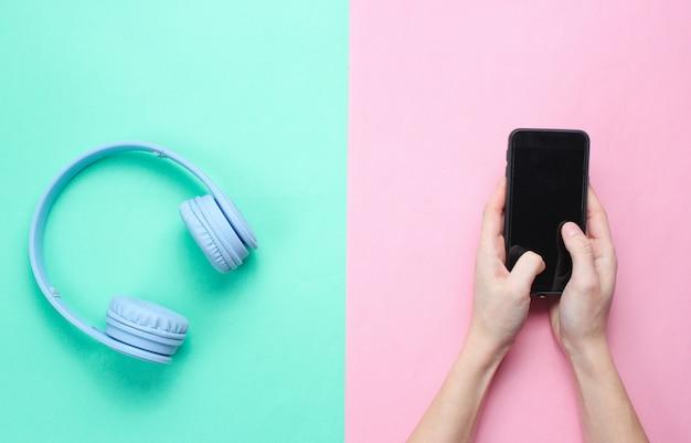 Manos femeninas que sostienen un teléfono inteligente moderno y auriculares sobre un fondo pastel