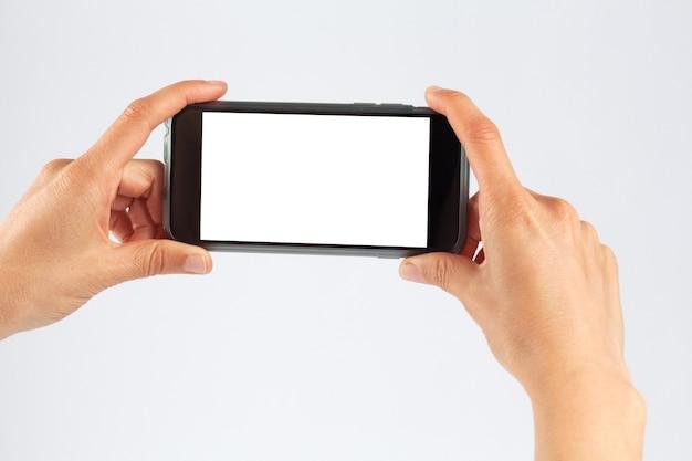 Manos femeninas que sostienen el teléfono móvil horizontalmente