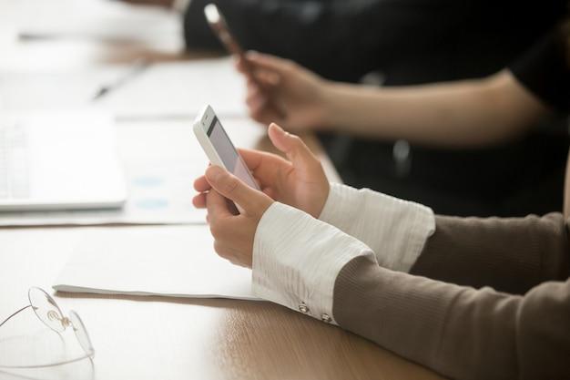 Manos femeninas que sostienen el teléfono móvil en la reunión de la oficina, opinión del primer