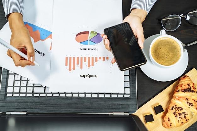 Manos femeninas que sostienen un teléfono y que hacen notas en gráficos en el papel. concepto de desayuno de negocios