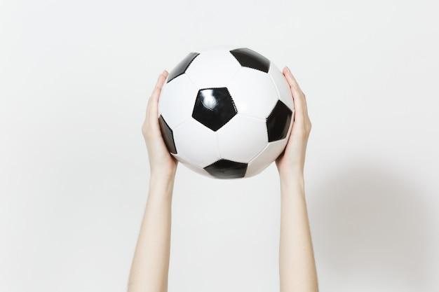 Manos femeninas que sostienen verticalmente la bola negra blanca clásica del fútbol aislada en el fondo blanco. deporte, fútbol, salud, concepto de estilo de vida saludable.