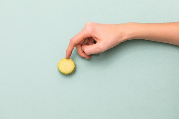 Manos femeninas que tocan la torta verde de los macarrones. vista superior, endecha plana. copyspace
