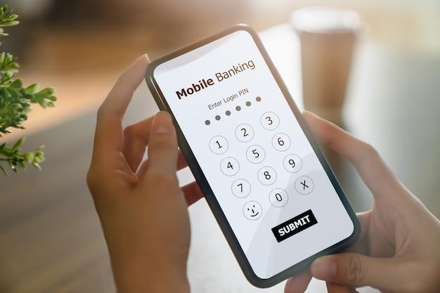 Manos femeninas que usan banca móvil en el teléfono inteligente e ingresan la contraseña para iniciar sesión en la aplicación.