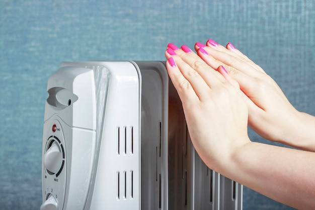 Manos femeninas en radiador de aceite eléctrico