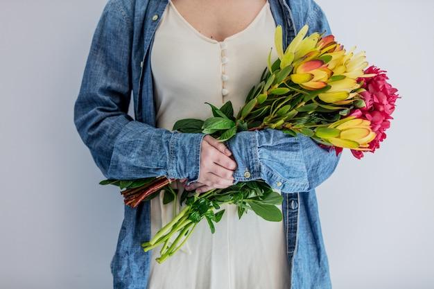 Manos femeninas con ramo de peonías y leucadendron