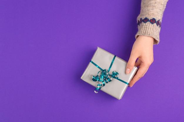 Manos femeninas con regalo envuelto en púrpura