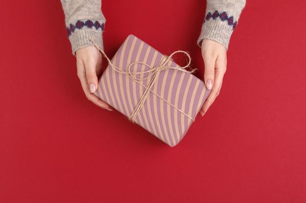 Manos femeninas con regalo de navidad sobre fondo rojo, vista superior, espacio de copia