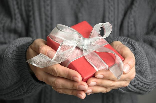 Manos femeninas con regalo rojo envuelto con cinta de plata. navidad. día de boxeo. de cerca.