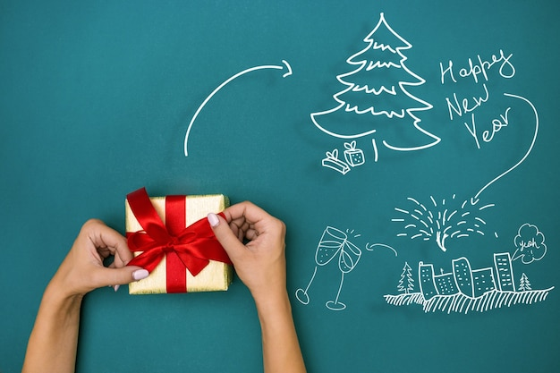 Las manos femeninas con regalo sobre fondo azul. concepto de navidad