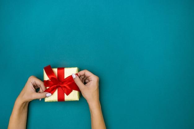 Las manos femeninas con regalo sobre fondo azul.
