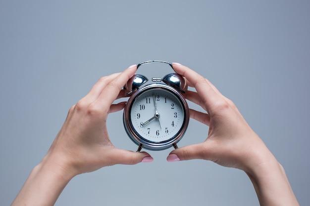 Manos femeninas y reloj despertador de estilo antiguo