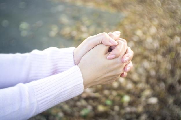 Las manos femeninas rezan en el jardín