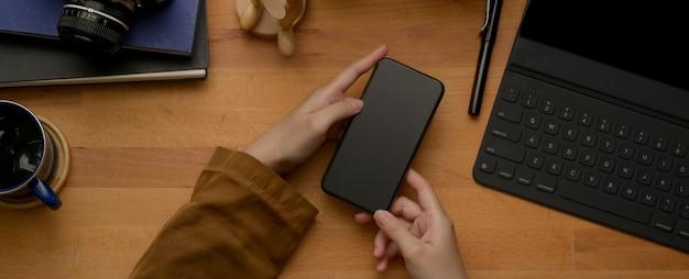 Manos femeninas con smartphone en mesa de madera con tableta digital, suministros y taza de café