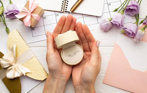 Manos femeninas sosteniendo el anillo de bodas