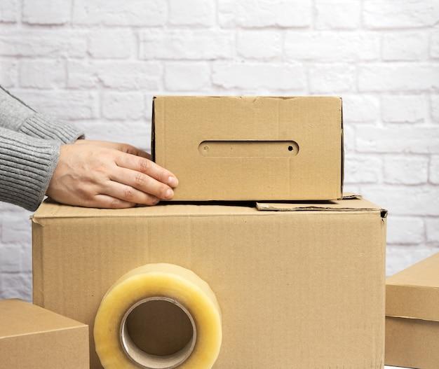 Manos femeninas sosteniendo una caja de cartón de papel marrón, concepto en movimiento, cerrar