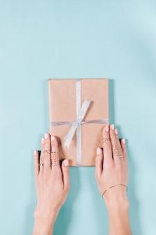 Manos femeninas sosteniendo una caja con regalo