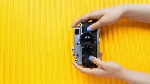 Manos femeninas sosteniendo la cámara de fotos vintage sobre fondo amarillo