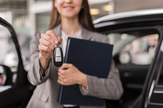 Manos femeninas sosteniendo una carpeta y las llaves del auto