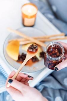 Manos femeninas sosteniendo una cuchara de mermelada de conos de abeto joven