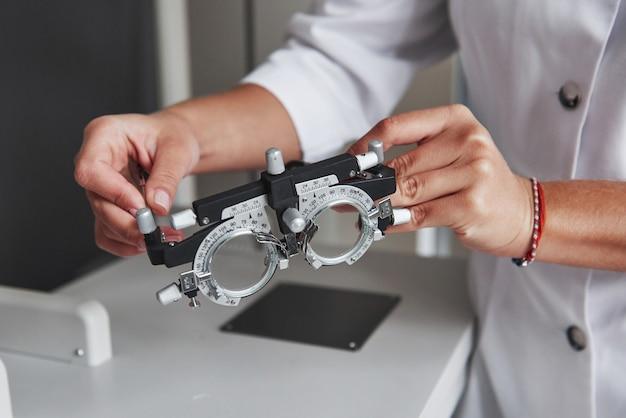 Manos femeninas sosteniendo el dispositivo óptico para pruebas oculares.
