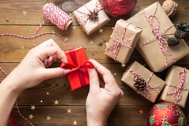 Manos femeninas sosteniendo, envolviendo la caja de regalo de navidad. grupo de cajas de regalo envueltas en papel artesanal, adornos rojos, brillo sobre mesas de madera. chritsmas fondo plano laico.