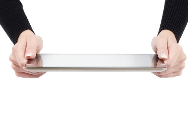 Manos femeninas sosteniendo un gadget de computadora tableta táctil con pantalla aislada