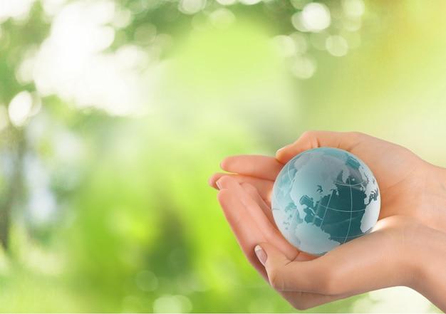 Manos femeninas sosteniendo globo de cristal sobre fondo