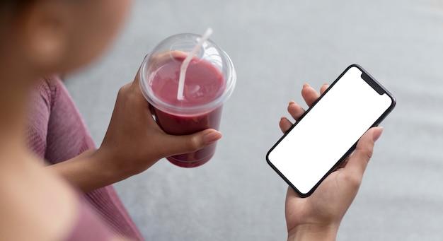 Manos femeninas sosteniendo un jugo de frutas y un teléfono inteligente con una pantalla en blanco