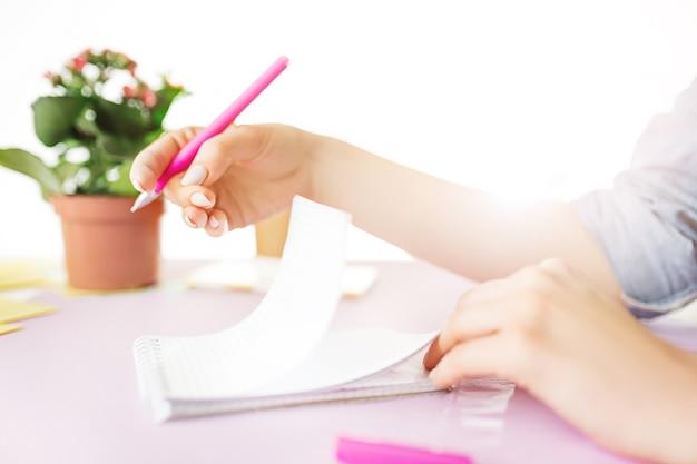 Manos femeninas sosteniendo la pluma, escribiendo. vista lateral de la mujer en el escritorio de color rosa de moda. mujer y lugar de trabajo estilizado. taza de café, teléfono, cuaderno. desayuno, teléfono, café. concepto del día de la mujer