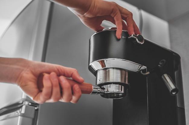 Manos femeninas sosteniendo el portafiltro y haciendo café aromático fresco en casa con una cafetera moderna