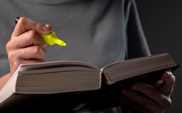 Manos femeninas sosteniendo resaltador amarillo y libro o libro de texto, tomando notas, subrayados. concepto de educación.