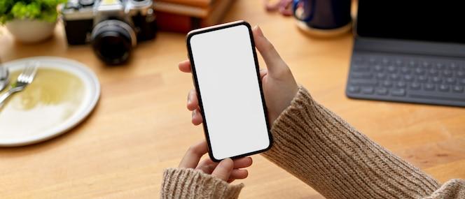 Manos femeninas sosteniendo simulacro de teléfono inteligente en la mesa de trabajo con tableta