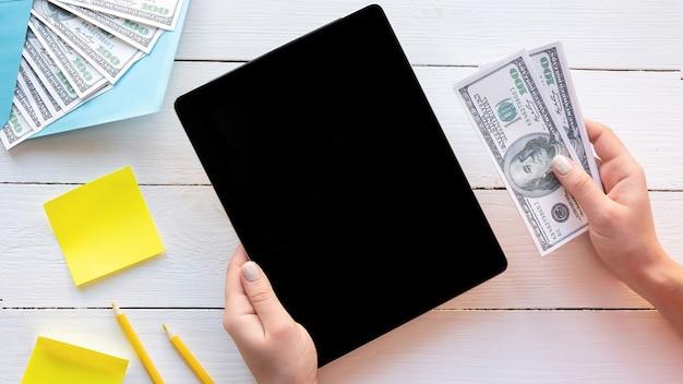 Manos femeninas sosteniendo una tableta y dinero. idea financiera
