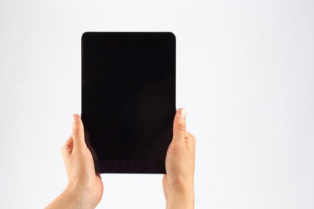 Manos femeninas sosteniendo una tableta verticalmente