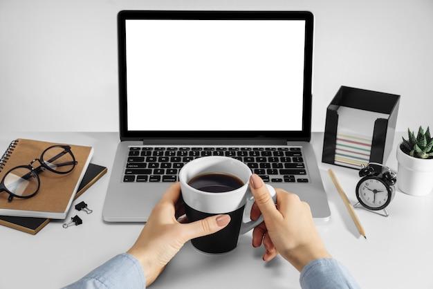Manos femeninas sosteniendo una taza de café y una computadora portátil con pantalla en blanco en blanco