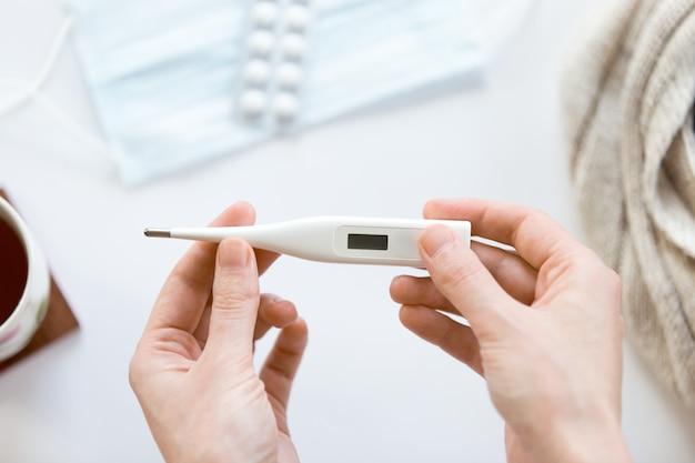 Manos femeninas sosteniendo termómetro electrónico sobre el blanco offic