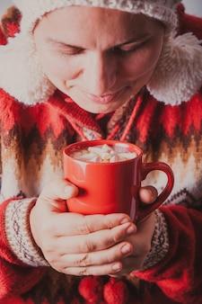 Manos femeninas sostiene una taza de cacao con malvavisco