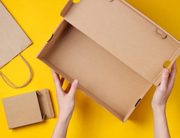 Las manos femeninas sostienen una caja de cartón vacía en un amarillo con una bolsa de papel y una caja. vista superior