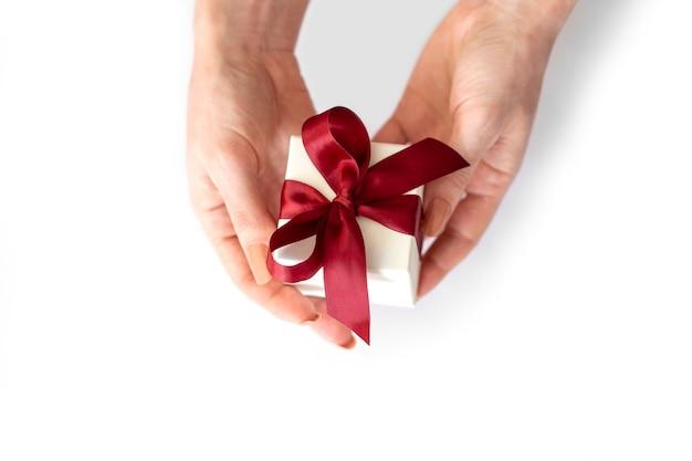Manos femeninas sostienen caja de regalo blanca con lazo rojo sobre fondo blanco.
