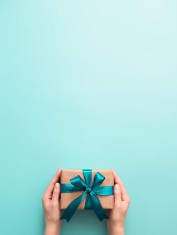 Manos femeninas sostienen caja de regalo, copyspace