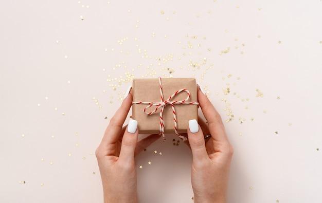 Manos femeninas sostienen caja de regalo en papel artesanal con cinta de año nuevo blanco-rojo y confettistars dorados en un espacio de copia de fondo beige, plano laical. navidad, boda