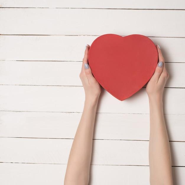 Las manos femeninas sostienen una caja roja en forma de corazón en la mesa de madera blanca