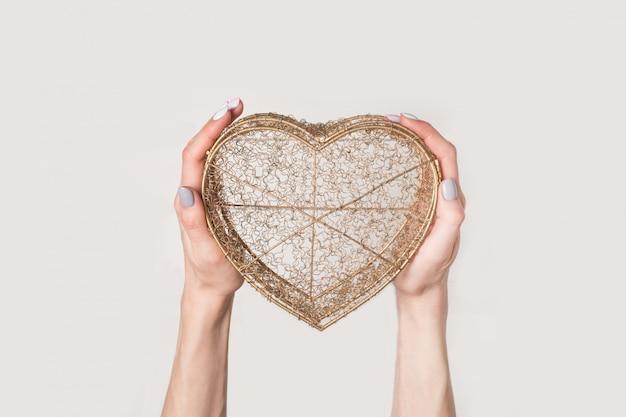 Manos femeninas sostienen caja transparente de alambre de metal en forma de corazón aislado