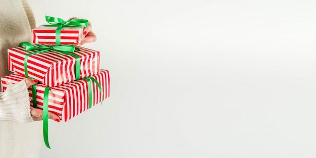 Manos femeninas sostienen cajas de regalo de navidad, champán y copas