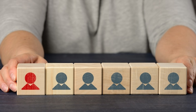 Las manos femeninas sostienen cubos de madera con figurillas. concepto de búsqueda de empleados, contratación de personal. selección de empleados talentosos y únicos para el avance profesional
