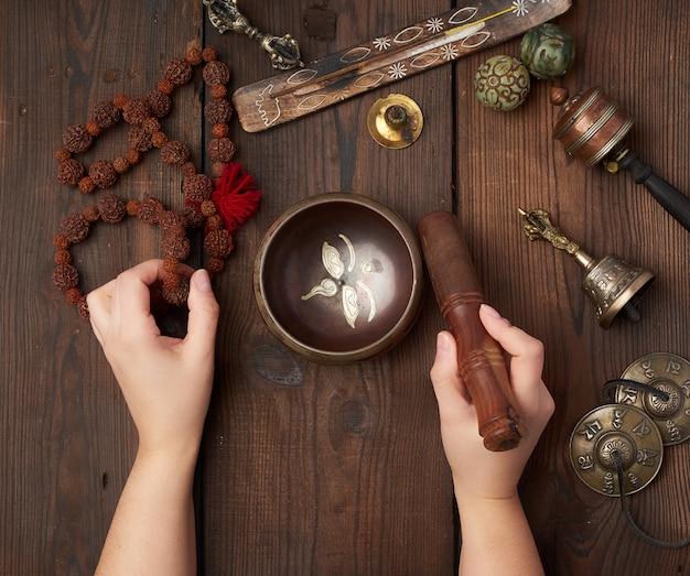 Las manos femeninas sostienen un cuenco tibetano de cobre y un palo de madera