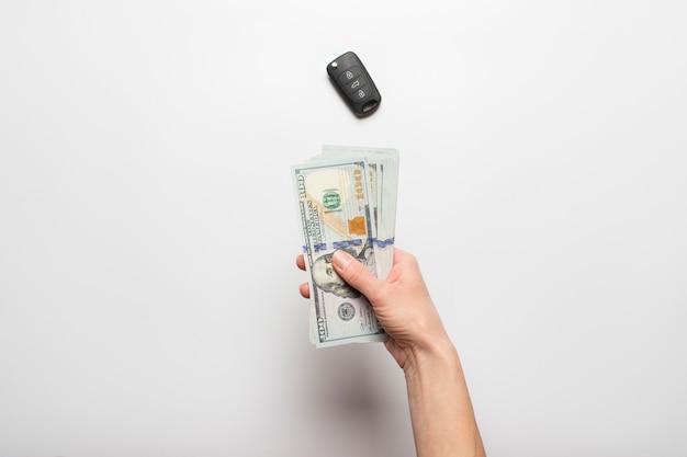 Manos femeninas sostienen, cuenta dinero, dólares en un fondo claro con una llave de coche. concepto de pago, compra, impuestos, alquiler, arrendamiento.