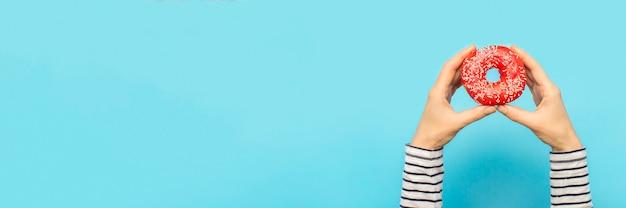 Las manos femeninas sostienen una dona en un espacio azul. concepto de tienda de confitería, repostería, cafetería. bandera. endecha plana, vista superior