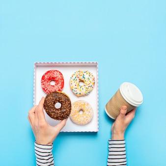 Las manos femeninas sostienen una dona y una taza de café en un espacio azul. concepto de tienda de confitería, repostería, cafetería. bandera.
