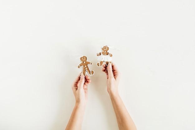 Manos femeninas sostienen galletas de hombre y mujer de jengibre aisladas sobre superficie blanca. endecha plana, vista superior